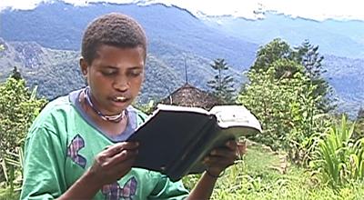 Young boy reading Yali Bible